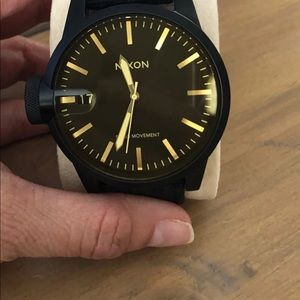 Like new men's black and gold Nixon watch.